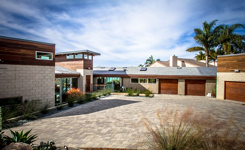 A view of the modern architecture of the home and the paver driveway, with native grasses incorporated to create movement in the landscape.