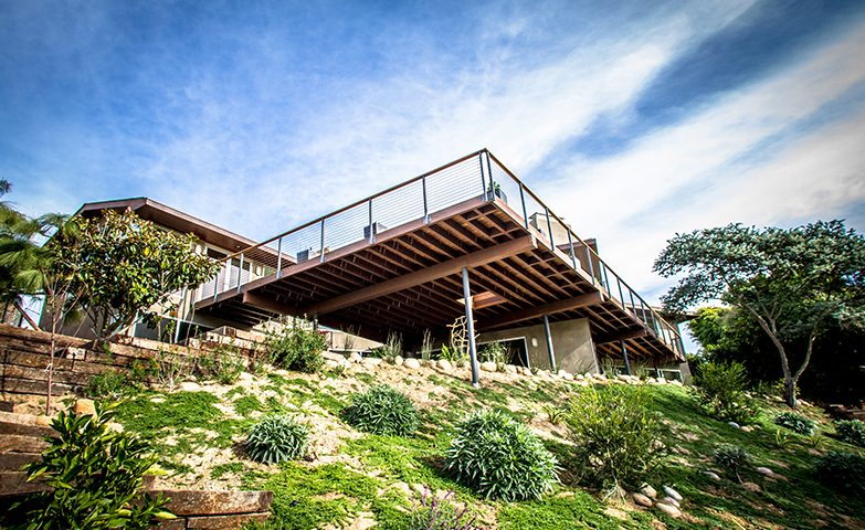 The expansive balcony off this modern home allows residents to enjoy the beautiful ocean views. The deck is constructed of cumaru wood, with cable rail wrapped around it. A native, low-water-use plant palette is featured in the foreground.