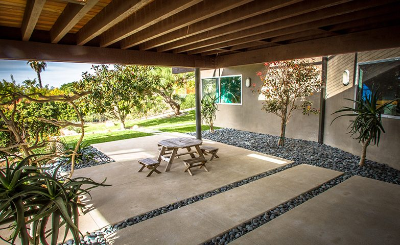 A modern concrete hardscape with Mexican beach pebble bands is featured, along with a low-water-use palette.
